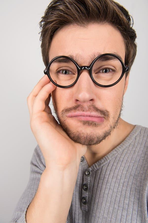 Gedeprimeerde nerd. Portret van jonge droevige mensen in oogglazen het houden royalty-vrije stock foto's