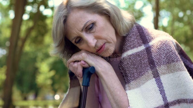 Gedeprimeerde oude vrouwenzitting op bank in tuin met wandelstok, eenzaamheid stock foto's