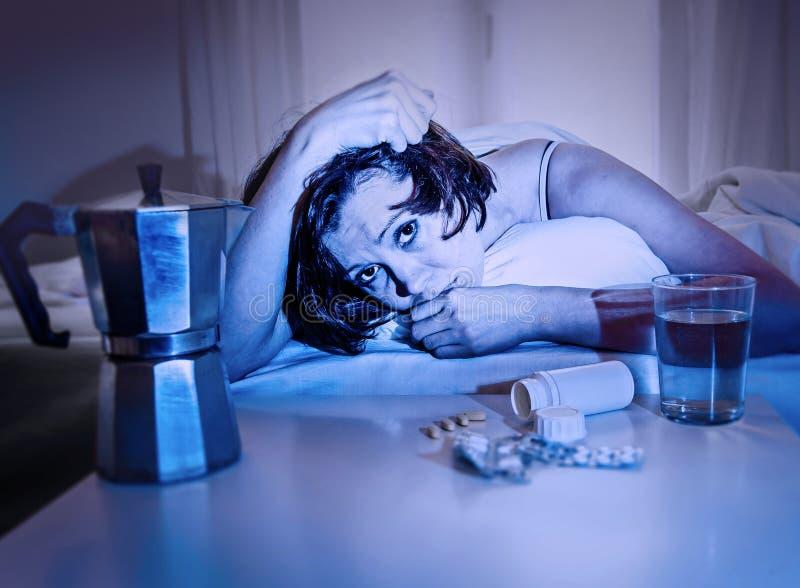 Gedeprimeerde vrouw in bed die aan kater na partijnacht lijden die waterkoffie en tabletten hebben stock afbeelding