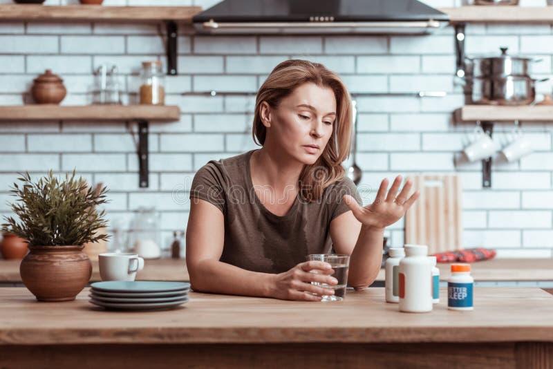 Gedeprimeerde vrouw die kalmeringsmiddelen na haar depressie nemen stock afbeelding