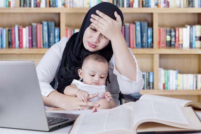Gedeprimeerde vrouw die met baby in bibliotheek werken royalty-vrije stock fotografie