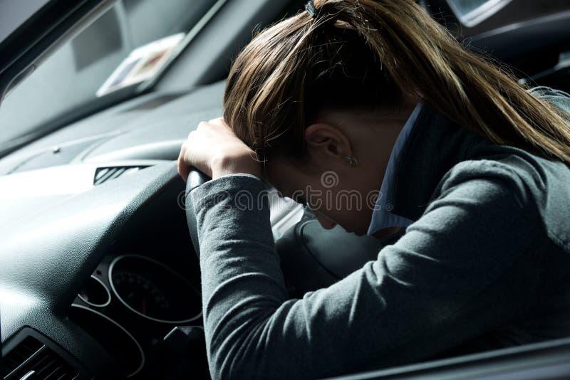 Gedeprimeerde vrouw in een auto stock foto's