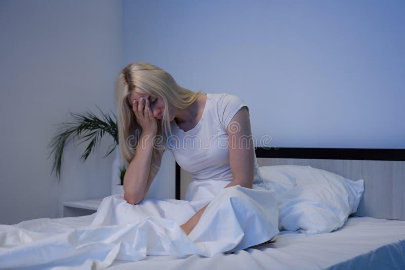 Gedeprimeerde vrouw wakker in de nacht, is zij uitgeput en lijdend aan slapeloosheid stock afbeeldingen