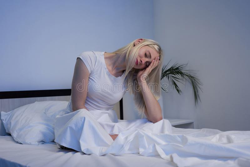 Gedeprimeerde vrouw wakker in de nacht, is zij uitgeput en lijdend aan slapeloosheid stock fotografie