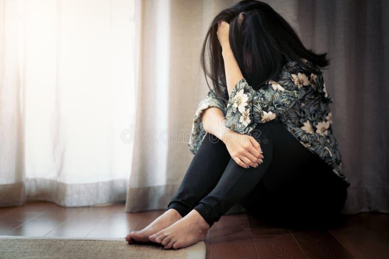 Gedeprimeerde vrouwen die dichtbij gordijn in alleen woonkamer zitten, droefheid, emotioneel concept stock foto's