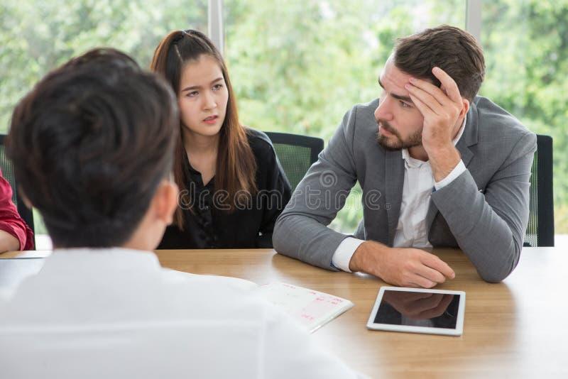 Gedeprimeerde werkgever tijdens een vergadering in bureau beklemtoonde zakenman het houden van handen op hoofd Ernstig stock fotografie