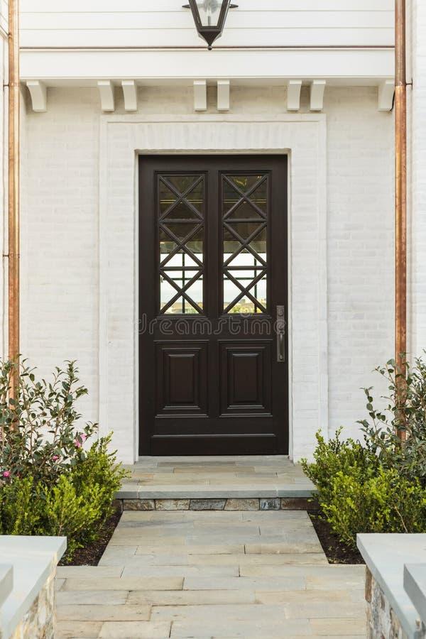 Gedetailleerde houten voordeur van wit baksteenhuis stock foto