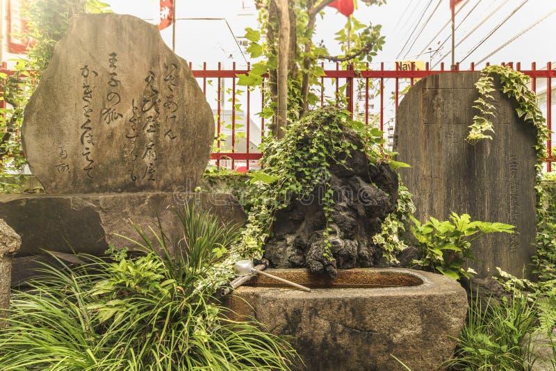 Gedicht des japanischen Dichters des 18. Jahrhunderts Ota Nanpo auf einem großen Stein im Schrein Shintoist Shozoku Inari stockbilder