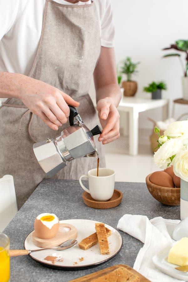 Gediend ontbijt, geroosterd brood die, zacht gekookt ei, vrouwelijke handen koffie van moka gieten stock foto