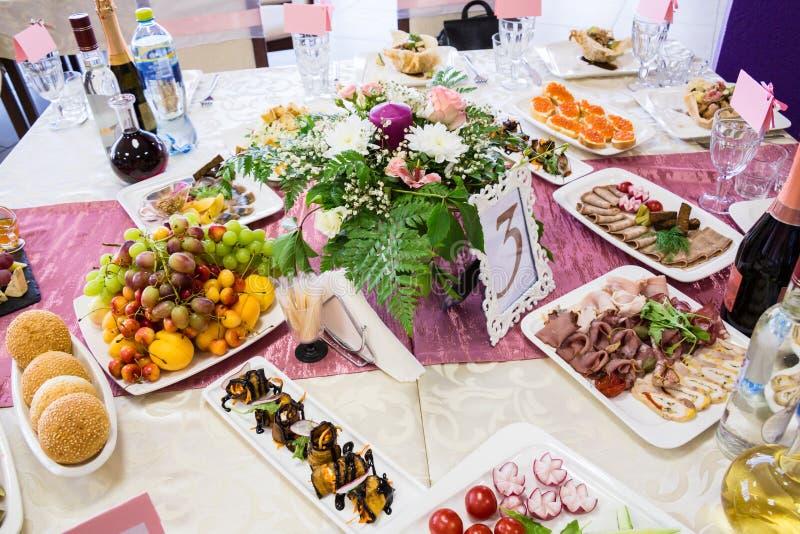 Gediende lijst bij het Banket Vruchten, snacks, delicatessen en bloemen in het restaurant Plechtig gebeurtenis of huwelijk royalty-vrije stock afbeeldingen