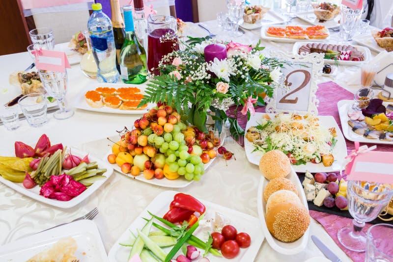 Gediende lijst bij het Banket Vruchten, snacks, delicatessen en bloemen in het restaurant Plechtig gebeurtenis of huwelijk stock foto