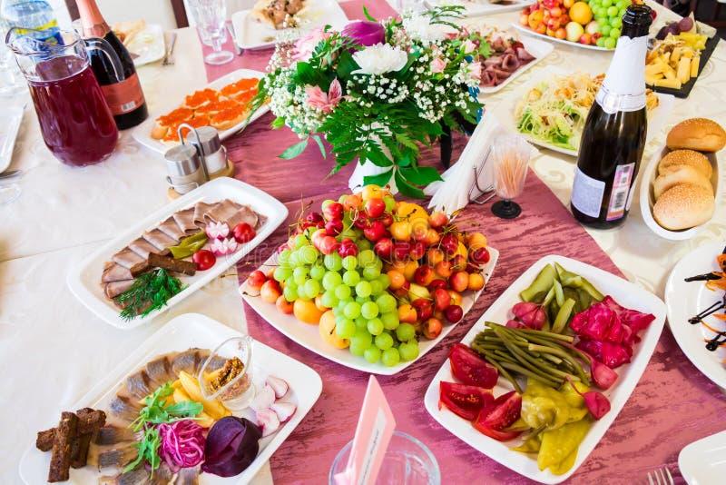 Gediende lijst bij het Banket Vruchten, snacks, delicatessen en bloemen in het restaurant Plechtig gebeurtenis of huwelijk stock afbeelding