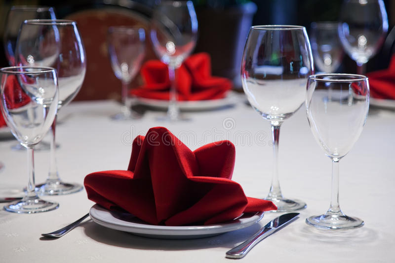 Gediende lijst in een restaurant met een wit tafelkleed, rode servetten, wijnglazen en bestek stock fotografie
