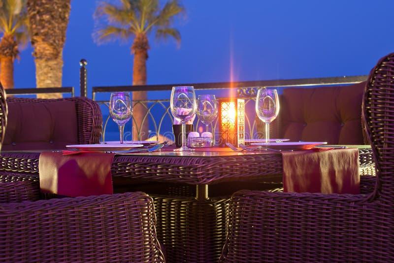Gediende lijst in een restaurant in openlucht in avondtijd stock foto's