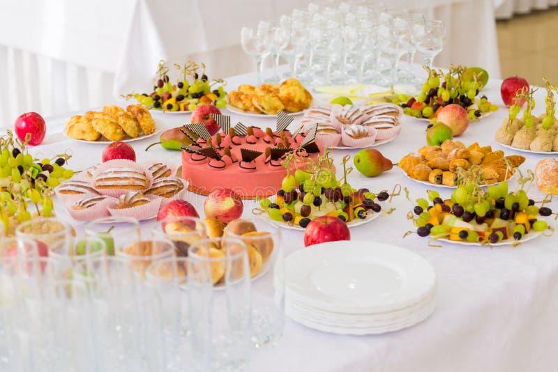 Gediende lijsten bij het Banket Desserts, fruit en gebakjes op het buffet Glas catering royalty-vrije stock fotografie