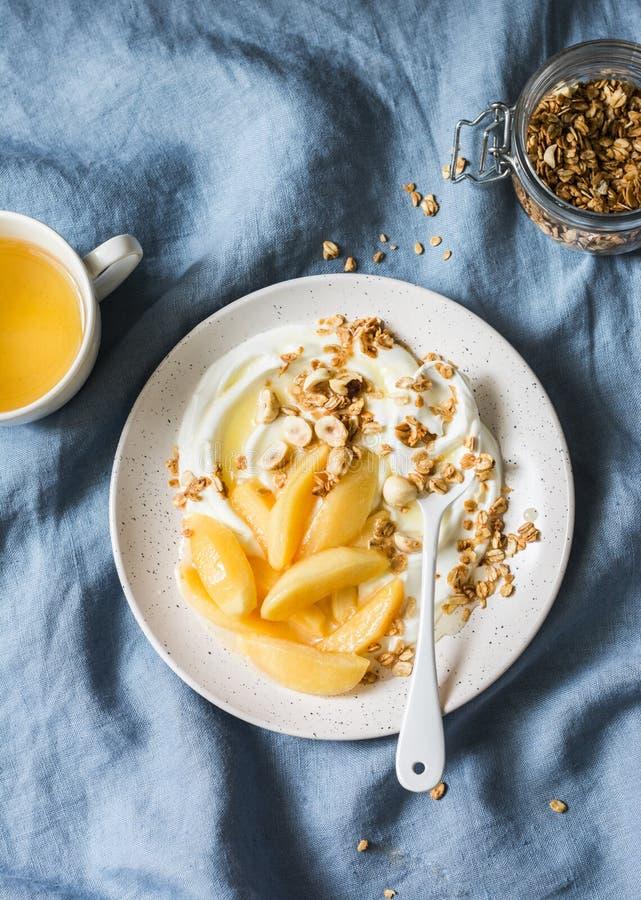 Gediende ontbijtlijst - gekarameliseerde kweepeer met Griekse yoghurt, granola en noten op een blauwe achtergrond, hoogste mening royalty-vrije stock afbeelding
