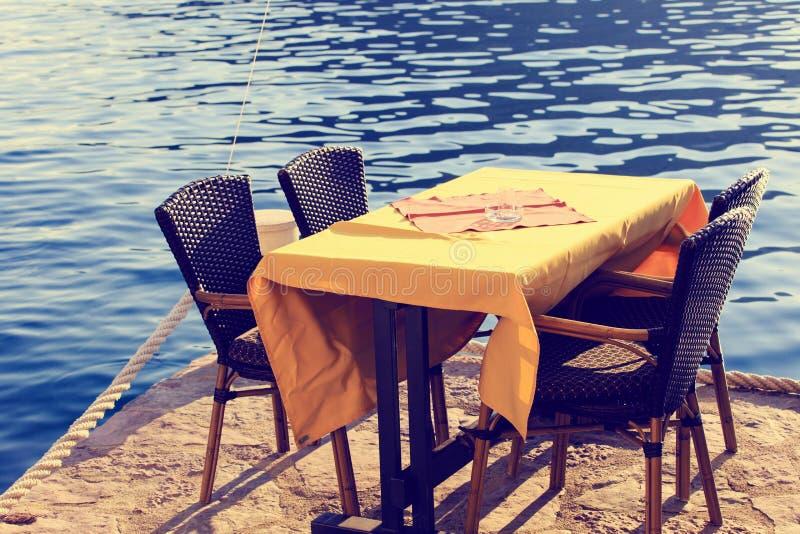 Gediente szenische Cafétabelle in dem Meer lizenzfreies stockbild
