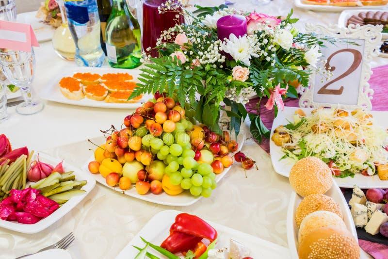 Gediente Tabelle am Bankett Früchte, Snäcke, Zartheit und Blumen im Restaurant Ernstes Ereignis oder Hochzeit lizenzfreies stockfoto