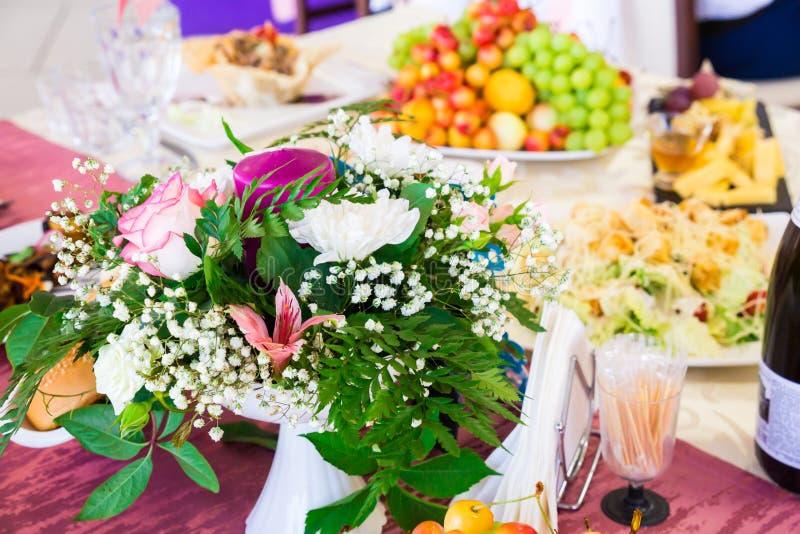 Gediente Tabelle am Bankett Früchte, Snäcke, Zartheit und Blumen im Restaurant Ernstes Ereignis oder Hochzeit stockfotografie