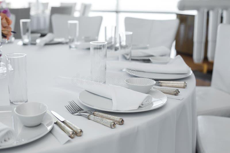 Gediente Tabelle in der Gastst?tte sauberer wei?er Tellerplan auf einer wei?en Tischdecke lizenzfreie stockbilder