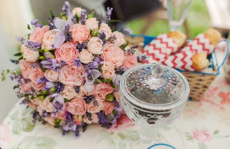 Gediente Tabelle draußen Blumenanordnung mit Lavendel und Rosen lizenzfreie stockfotografie