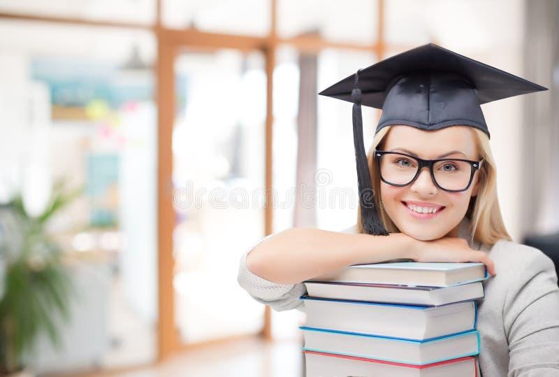 Gediplomeerd studentenmeisje in vrijgezelhoed met boeken stock foto