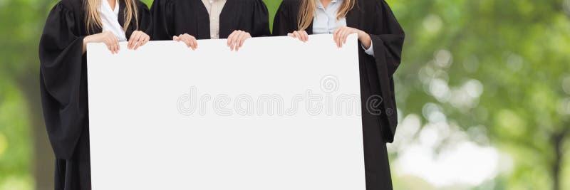 Gediplomeerde mensen die een lege kaart houden tegen groene vage achtergrond royalty-vrije stock foto's