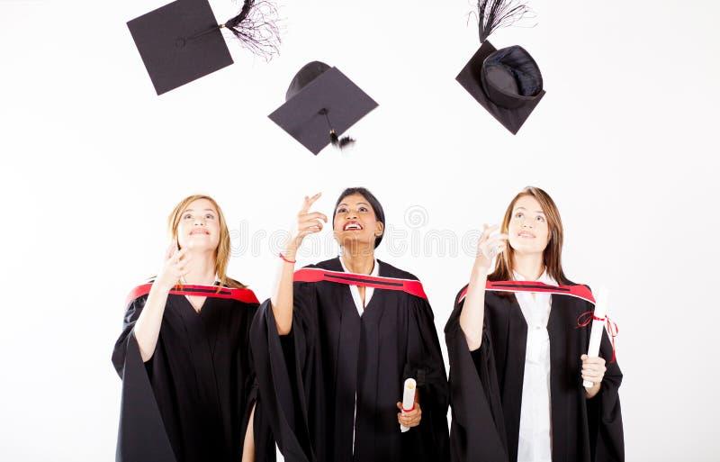 Gediplomeerden die graduatiekappen werpen stock fotografie