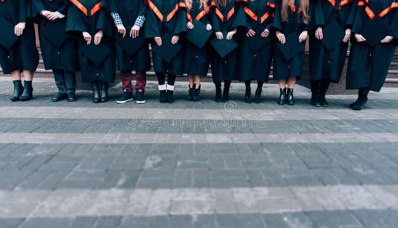 Gediplomeerden die hun hoeden in handen houden Gediplomeerden die robes en hoeden in hun handen dragen Groep studenten in vrijgez stock foto's