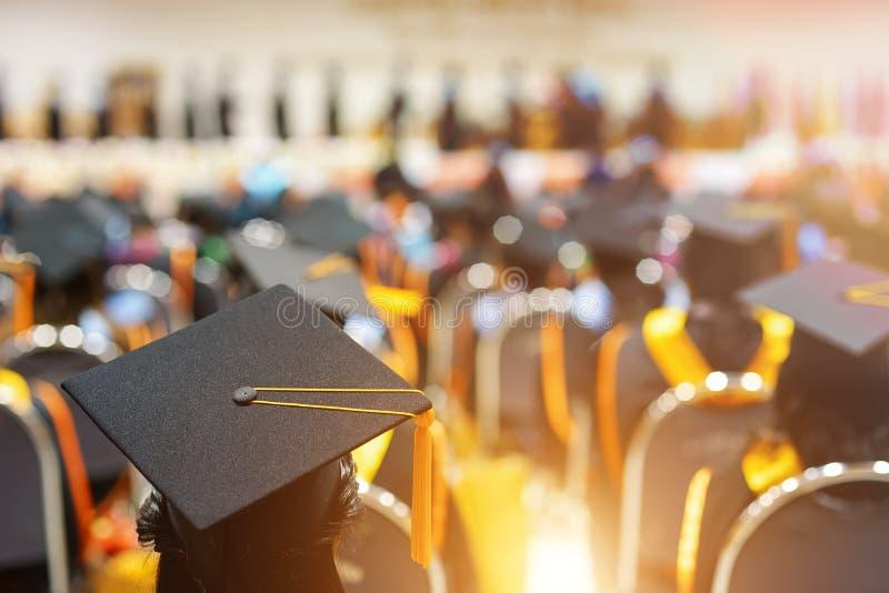 Gediplomeerden in graduatieceremonie stock afbeeldingen