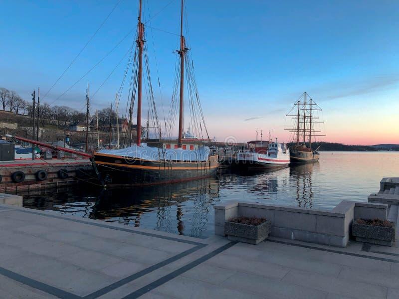 Gedokte boten in Oslo Noorwegen, zonsondergang stock foto
