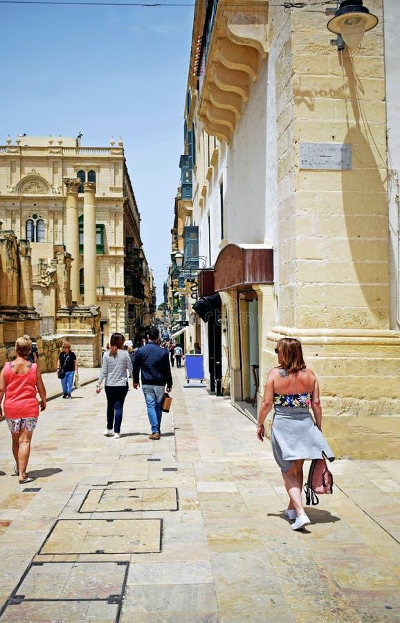 Gedränge und hastige Geschäftigkeit des Stadtlebens in Valletta, jeder man geht über ihr Alltagsleben, einige ist der sehende Sta lizenzfreies stockfoto