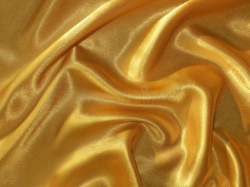 Gedrapeerde gouden (oranje) satijnachtergrond stock afbeelding
