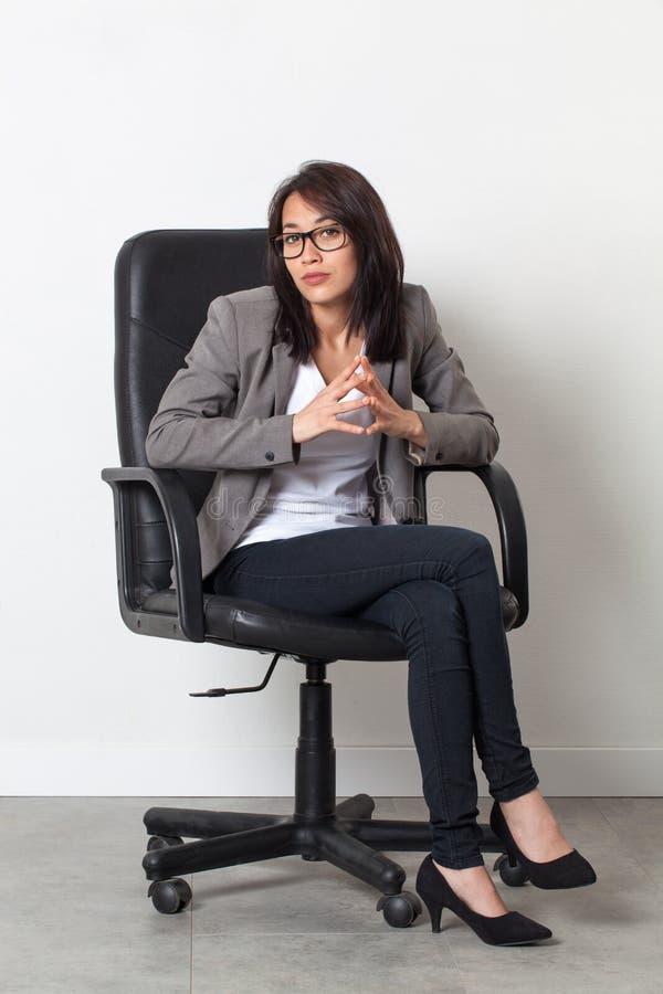 Geduldige Geschäftsfrau, die im Bürostuhl für ihren Startjob aufwirft lizenzfreies stockfoto