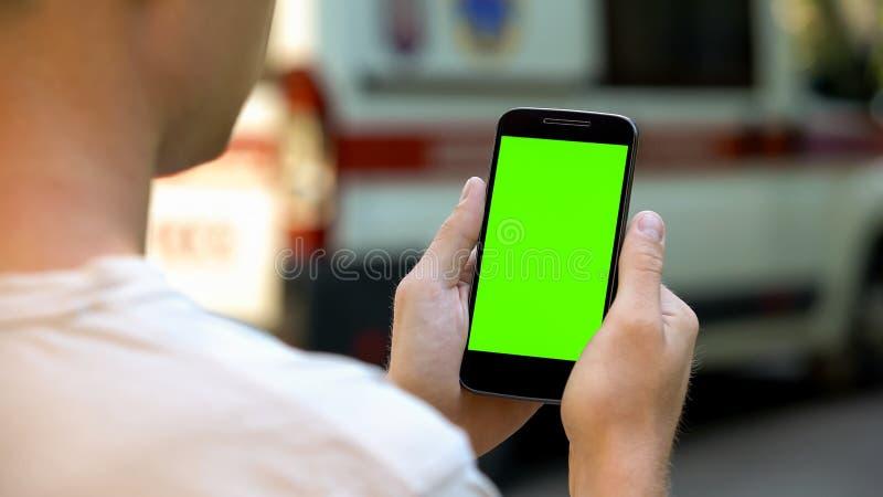 Geduldige het gebruiken cellphone om testresultaten, ziekenwagen op achtergrond, close-up te lezen royalty-vrije stock foto