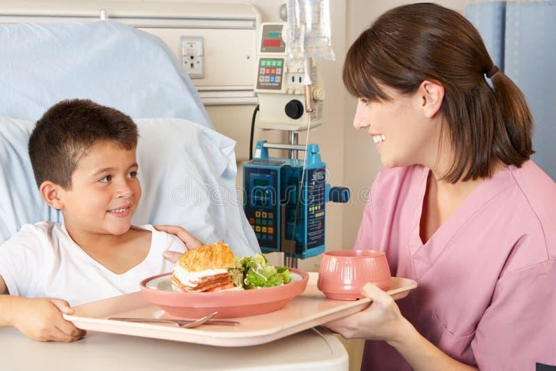 Geduldige Maaltijd van het Kind van de verpleegster de Dienende in het Bed van het Ziekenhuis royalty-vrije stock afbeelding