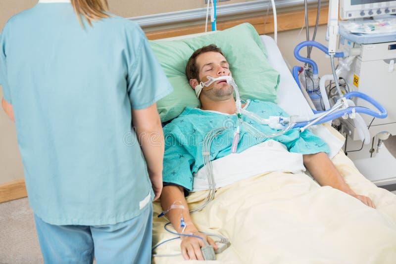 Geduldige Slaap met Verpleegster Standing By royalty-vrije stock fotografie