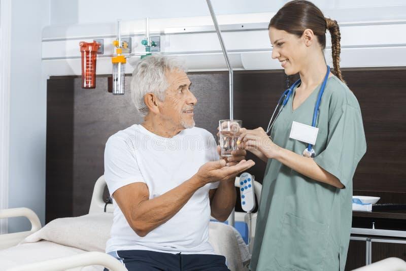 Geduldiges empfangendes Wasser-Glas und Pille von der weiblichen Krankenschwester stockfotografie