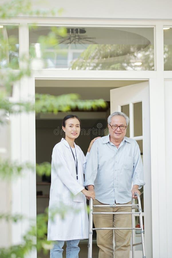 Geduldiges Gehen mit Krankenschwester lizenzfreie stockbilder