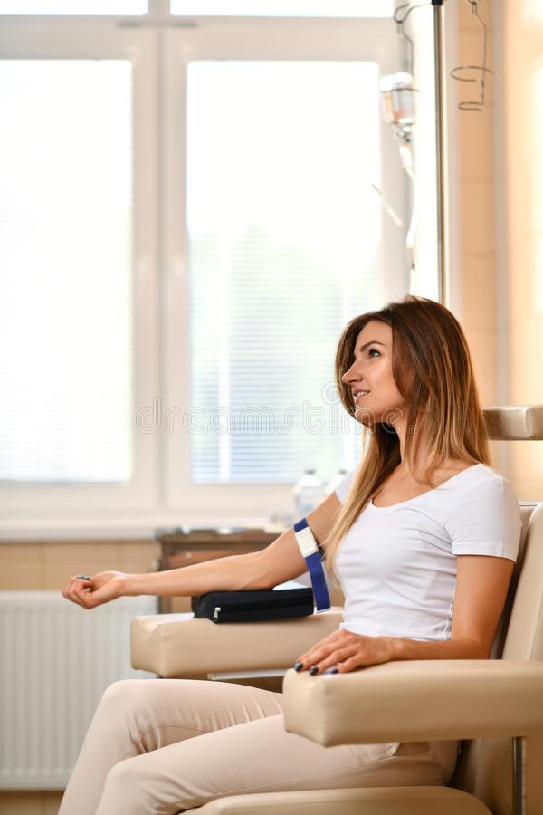 Geduldiges Warten der Frau in Doktorkabinett die Blutsammlung MEDIZINISCHES Konzept stockfoto
