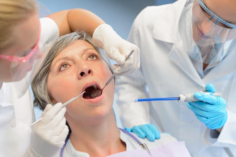 Geduldiges Zahnarztteam der zahnmedizinischen Kontrollälteren Frau lizenzfreies stockbild
