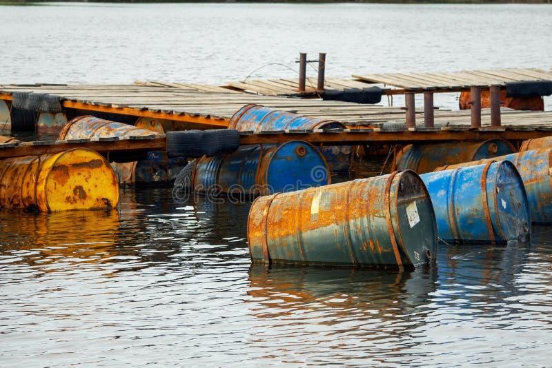 Gedumpte de oorzakenverontreiniging van olietrommels in het water royalty-vrije stock fotografie