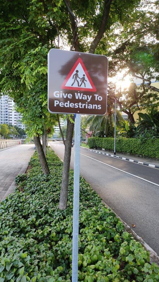 Geef aan de raad van het voetgangersteken op weg uiting stock fotografie