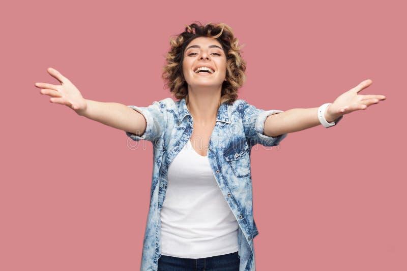 Geef me omhelzing Portret van gelukkige jonge vrouw met krullend haar in toevallig blauw zich met opgeheven wapens bevinden om te stock foto's