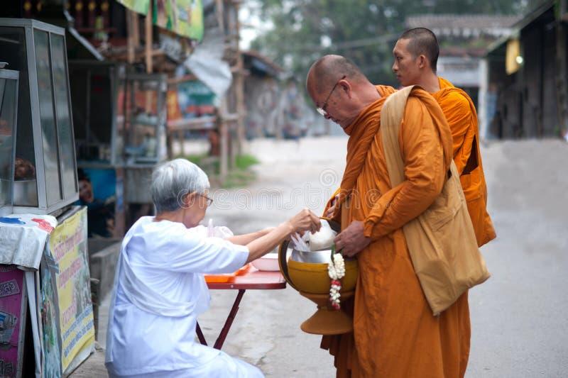 Geef voedsel aan een Boeddhistische monnik. stock afbeelding