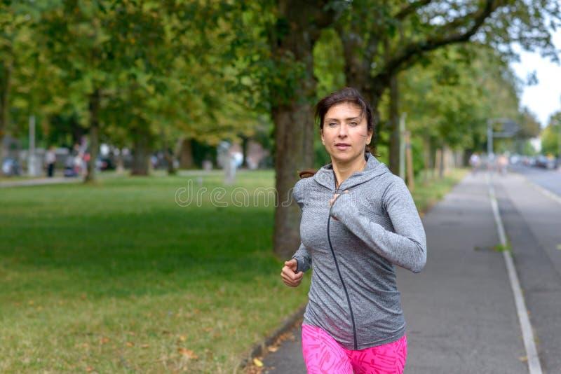 Geeignete erwachsene Frau, die auf konkretem Bürgersteig läuft stockfotografie