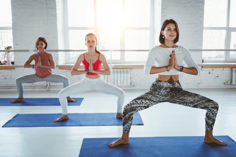 Geeignete erwachsene Frauen, die Yogahaltungen in der Eignungsklasse üben Gruppe der gesunden starken Frau, die geeignete Übungen stockfoto