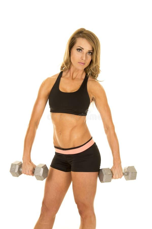 Geeignete Frau in den schwarzen kurzen Hosen und im Spitzengriff zwei Gewichte unten lizenzfreie stockbilder