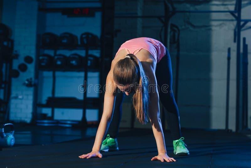 Geeignete Frau in der bunten Sportkleidung, die burpees auf einer Übungsmatte in einem grungy Industrietyp Raum tut lizenzfreie stockbilder