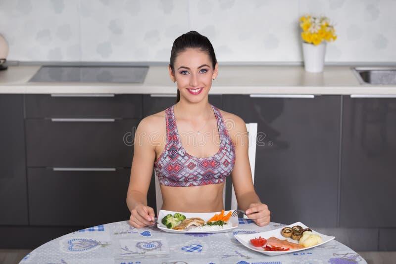 Geeignete Frau der Junge in der Küche, gesunde Mahlzeit vorbereitend stockfoto